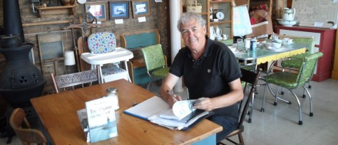 Mike Martin sitting at a table siging books